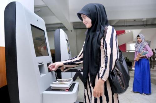 Seorang mahasiswa meminjam buku melalui fasilitas otomasi rfid perpustakaan uin Sunan Kalijaga